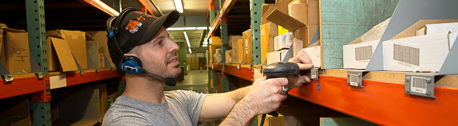 Photo of IOB employee scanning bar codes on stored boxes in warehouse.