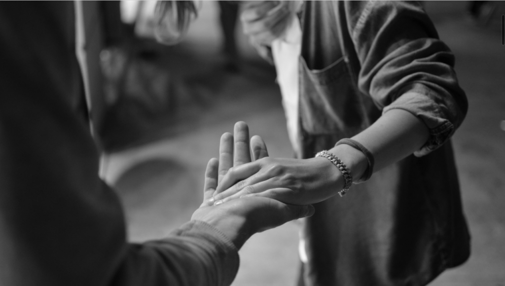 Black and white photo of person taking another person's hand to help them