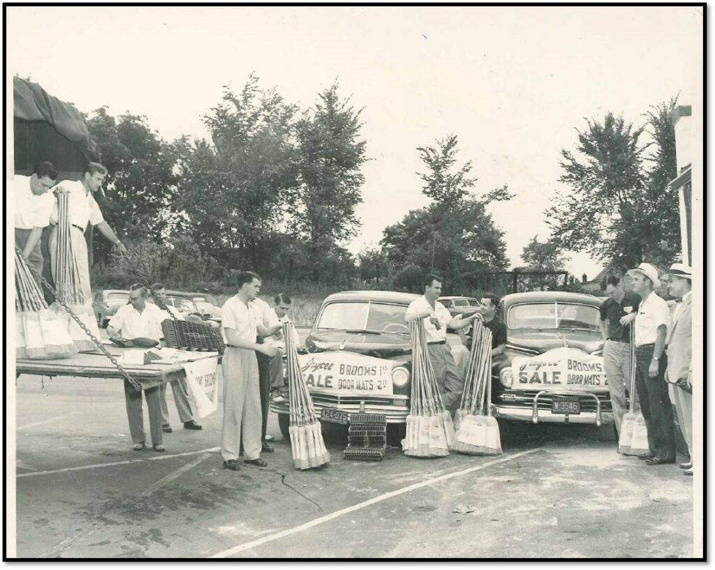 Black and white photo of people selling brooms made by the Industries of the Blind back in the 1960's.