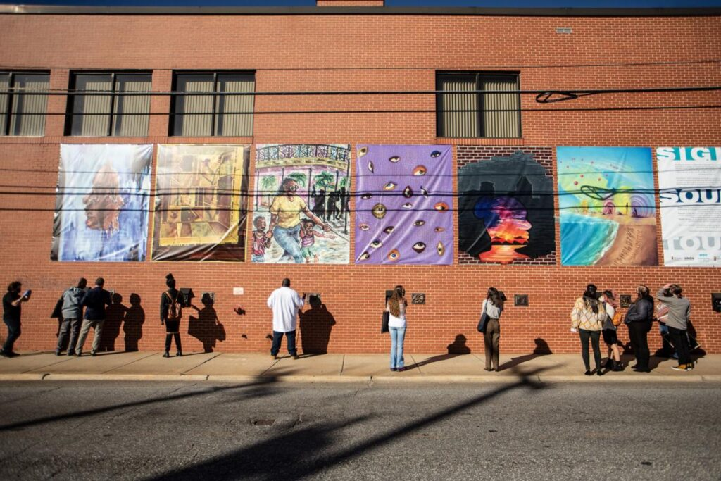 Artists and employees listen and look at UNCG's College of Visual and Performing Arts and the Industries of the Blind public art piece on the Industries of the Blind building in Greensboro on Nov. 20.