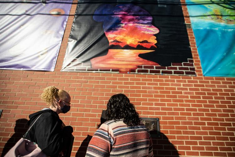 Employees at Industries of the Blind, listen to part of UNCG's College of Visual and Performing Arts and the Industries of the Blind public art piece on the Industries of the Blind building in Greensboro on Nov. 20. At left is Kelly McKinney. At right is Afiya Jackson.