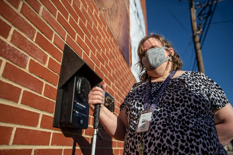 Vickie Burke, an employee at Industries of the Blind, listens to part of UNCG's College of Visual and Performing Arts and the Industries of the Blind public art piece on the Industries of the Blind building in Greensboro on Nov. 20.