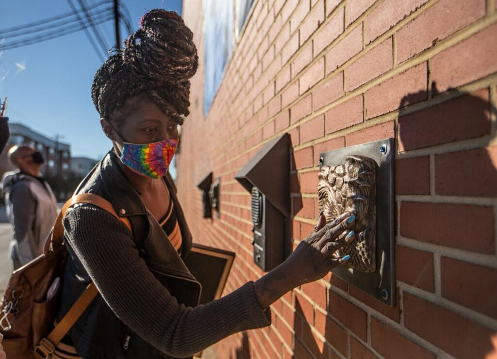 LaToya McEachean, an employee at Industries of the Blind, touches a relief sculpture at UNCG's College of Visual and Performing Arts and the Industries of the Blind public art piece on the Industries of the Blind building in Greensboro on Nov. 20.